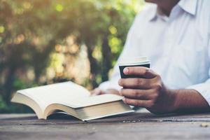 man leest een boek in zijn handen foto