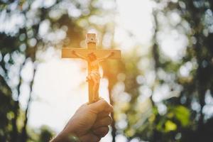 handen met een houten kruis over de hemel foto