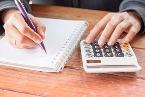 close-up van een persoon die met een rekenmachine schrijft