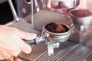 barista die espresso-gronden aanbrengt