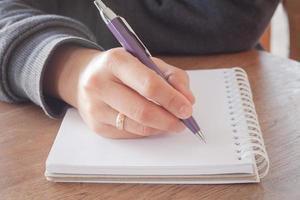 close-up van een persoon die in een notitieboekje schrijft
