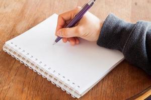 close-up van een hand die in een notitieboekje schrijft
