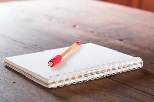 rood potlood op een notitieblok op een tafel