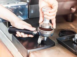 barista die espresso-gronden aanstampt