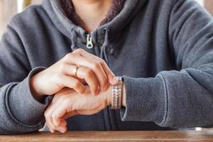 persoon die een hoodie draagt en de tijd controleert