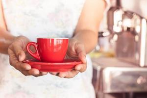 vrouw met een rode koffiekopje