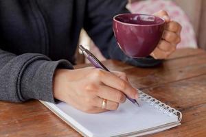 persoon die een koffiekopje houdt en in een notitieblok schrijft