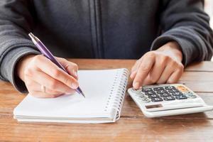 persoon die in een notitieboekje met een rekenmachine schrijft