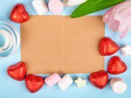 bovenaanzicht van bruin papier met hartvormige chocolaatjes