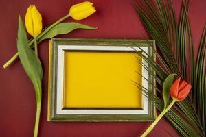 bovenaanzicht van een leeg afbeeldingsframe met tulpen en een palmblad