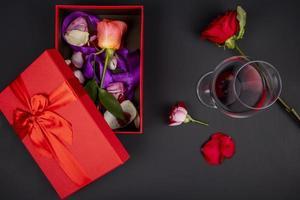 bovenaanzicht van een glas rode wijn met een doos bloemen