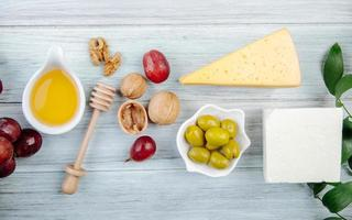 bovenaanzicht van kaas met honing, druiven, noten en olijven