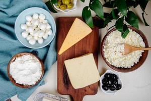 bovenaanzicht van kaas in verschillende kommen en op een snijplank