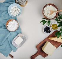 bovenaanzicht van kaas in kommen en op een snijplank met kopie ruimte