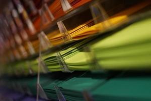 regenboogkleurige papieren in planken