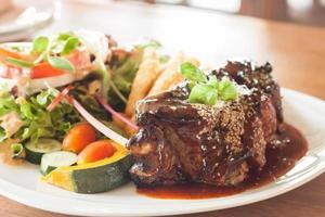 varkensribbetjes met pikante saus en een salade