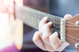 close-up van handen op een gitaar