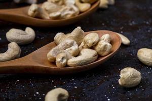 cashewnoten op houten lepels op een zwarte achtergrond