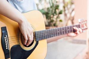 close-up van een persoon die buiten een akoestische gitaar speelt
