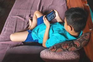 jongen spelen van spelletjes op een telefoon foto