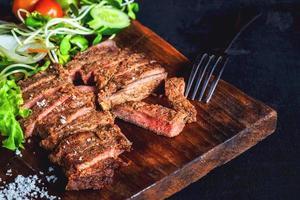 biefstuk op een houten plaat foto