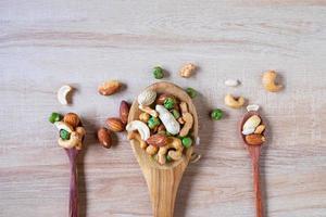 gemengde noten op houten lepels foto