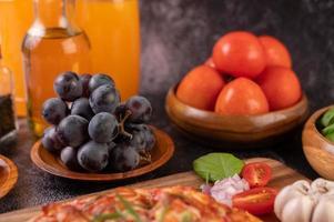 zwarte druiven met tomaten sinaasappelsap en pizza foto