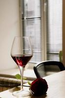 rode wijn in een glas met een roos