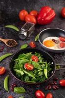 gebakken boerenkool in een sauspan met tomaten en paprika's