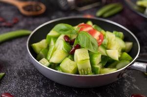 komkommers met tomaten in een sauspan