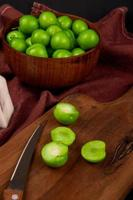 zure groene pruimen in een houten kom en op een tafel