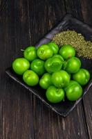 zure groene pruimen op een zwarte schaal foto