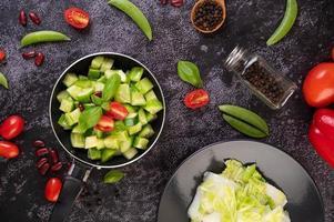 komkommers roergebakken met tomaten in een koekenpan plat leggen