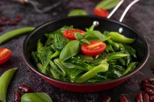 roergebakken boerenkool in een pan met tomaten