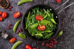 roergebakken boerenkool in een pan met tomaten en paprika, bovenaanzicht