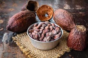 cacaobonen in een kom op een tafel foto