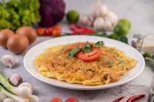 omelet op een wit bord met tomaten en koriander