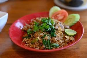varkensvlees gebakken rijst die op de plaat is, met een halve citroen op houten tafel