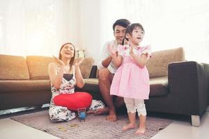 kind met haar ouders die thuis op de vloer spelen foto