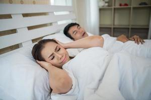 slapende vrouw blokkeert oren met man snurken in bed