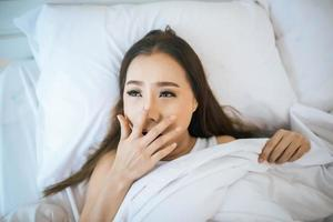 vrouw wordt wakker in haar bed, lui in de ochtend foto