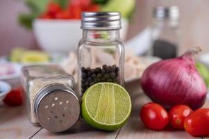 schijfjes limoen met twee shakers en andere groenten op een houten tafel foto