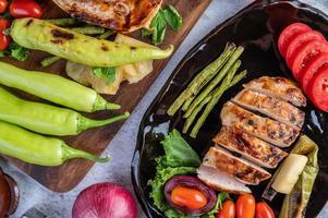 kippenbiefstuk met salade groenten op een zwarte plaat foto