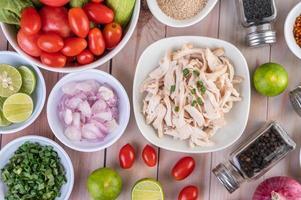 gekookte stukjes kip met groenten en kruiden op een houten tafel