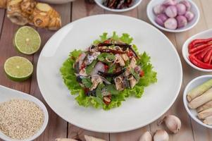 gefrituurde makreel gegarneerd met laos, paprika, munt, rode ui in een witte schotel.
