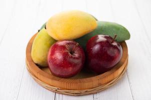 appels en mango's in een houten kom
