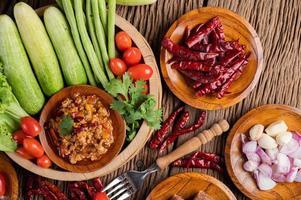 varkensvlees in een houten kom met komkommer, kousenband en bijgerechten