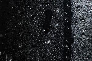druppels op doorzichtig plastic blad, zwarte achtergrond