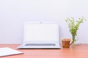 laptop, beker en bloem op het bureau