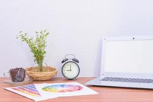 laptop, documenten en bloem op het bureau